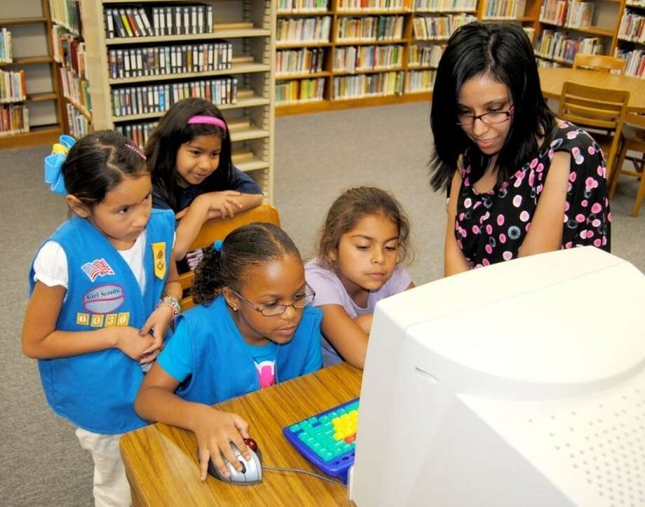 Doug McDonough/Plainview HeraldLeader Liz Flores (right) helps Daisy Scouts in Troop 6036 learn how to look up books about Earth Day during a visit to Unger Memorial Library on Friday. Girl Scouts nationwide are celebrating the organization's centennial this year. To mark that occasion the library is displaying local Girl Scout memorabilia. Watching Alina Thomas use a computer mouse to scroll through the computerized library listings are Gabrielle Aleman (left), Zolema Mariscal and Nayeli Mariscal.