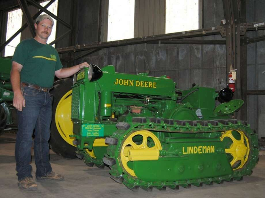 Doug McDonough/Plainview HeraldCody Gruhlkey of Kress stands beside his 1946 John Deere crawler tractor, one of 80 tractors displayed Saturday at the 20th annual Ollie Liner Antique Tractor Show. President of the Texas Plains Two-Cylinder Club, Gruhlkey said his restoration involved about 320 hours of labor from late 2010 to mid-2011. The tractor was shipped from the factory without wheels and axles. The tracks were added by the Lindeman Brothers so the tractor could plow under trees in a California walnut grove. It was the first crawler-style tractor available through John Deere. Gruhlkey had nine restored tractors in Saturday's show.