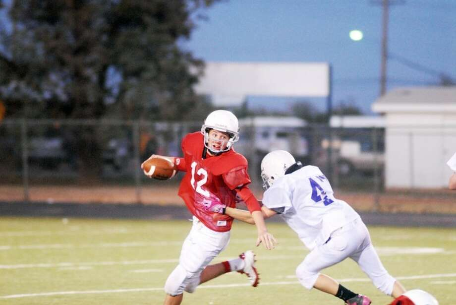 7th grade red quarterback Wrangler Haresnape scrambles away from the outstretched arms of a Canyon defender. Haresnape helped lead the squad to an 8-0 season. Photo: Plainview Herald Archives