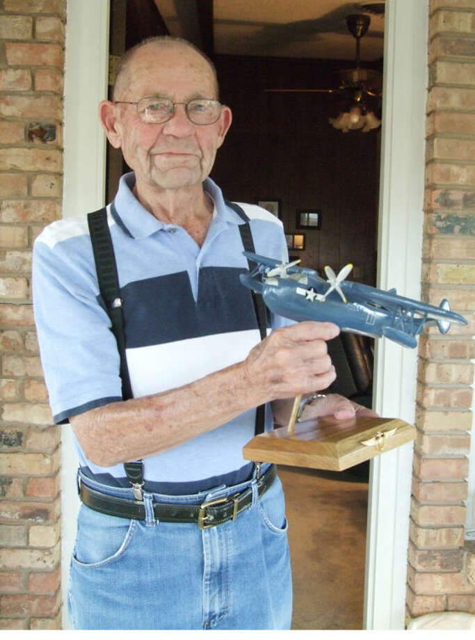 World War II veteran Lloyd Belk, 87, holds a model of a PBM Martin Mariner, a replica of the plane he flew during the war. Photo: Shanna Iverson/Plainview Herald