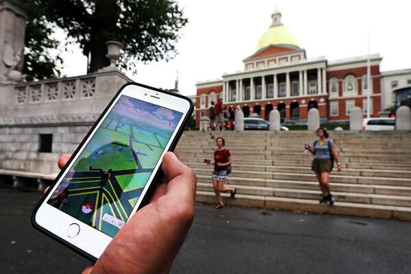 """A """"Pokemon Go"""" player shows his mobile phone while walking through the Boston Common, outside the Massachusetts Statehouse in Boston. Historical markers dot the landscape of old cities, barely noticed by passers-by. The founder of the volunteer-based historical markers website that licensed its data to game-maker Niantic Labs five years ago said he hopes enough people take their eyes off the Pokemon they're trying to catch to read the history on the markers."""