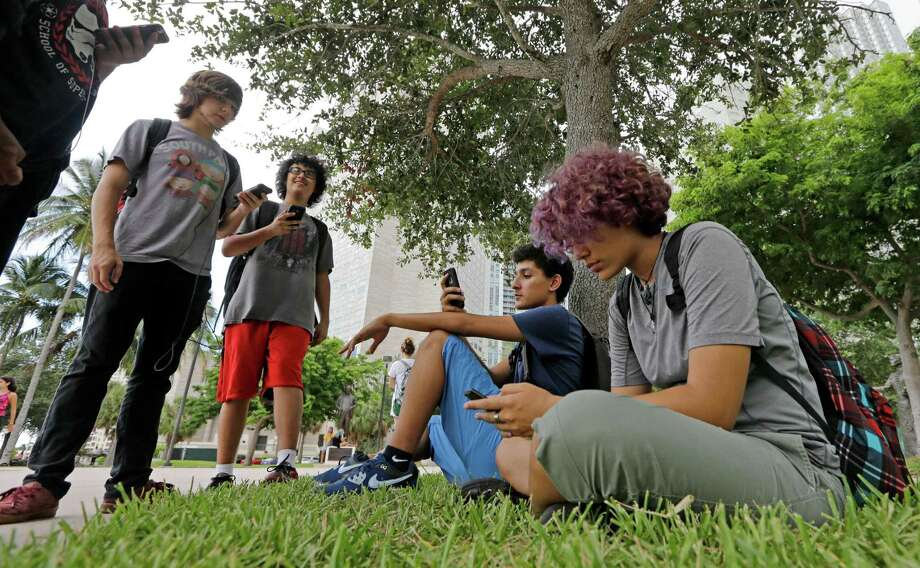 "Pokemon Go players Ana Valentina Ojeda, right, and Jaeden Valdespino, second from right, check their smartphones as they look for Pokemon at Bayfront Park in downtown Miami as the ""Pokemon Go"" craze has sent legions of players hiking around cities and battling with ""pocket monsters"" on their smartphones. Photo: Alan Diaz /AP / Copyright 2016 The Associated Press. All rights reserved. This material may not be published, broadcast, rewritten or redistribu"