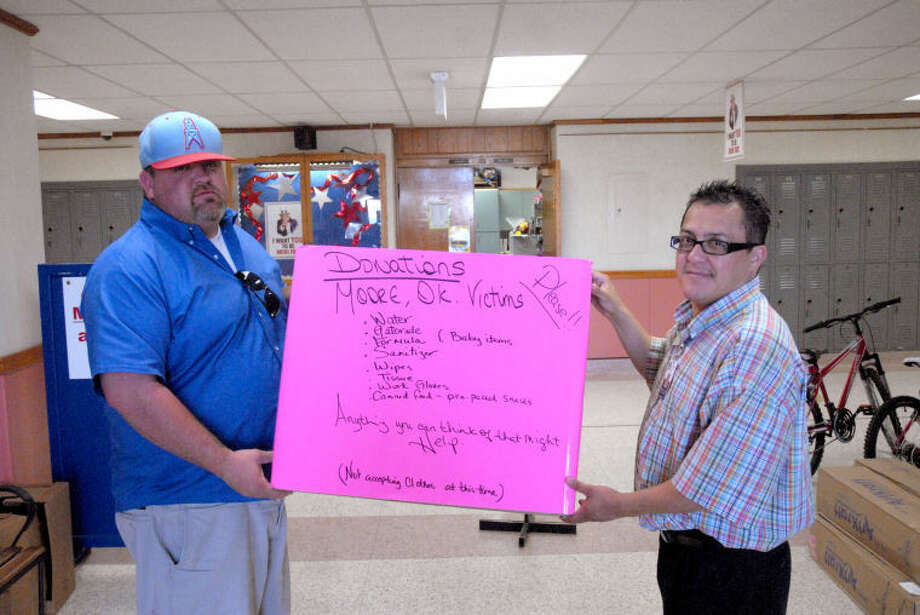 Cody Lindleman (left) delivers a drop box for donations to Ash assistant principal Jeff DeLaGarza Tuesday afteroon. Donations boxes can be found in a number of locations for Moore relief efforts. Photo: Homer Marquez/Plainview Herald