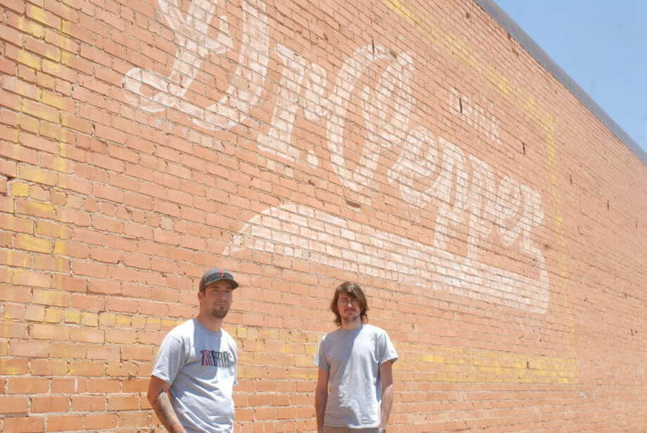 Artists Angel Azua and John Riddle stand in front of their next project as they look to restore the classic Dr Pepper sign located on the side of AC Uniforms and More. Photo: Homer Marquez/Plainview Herald