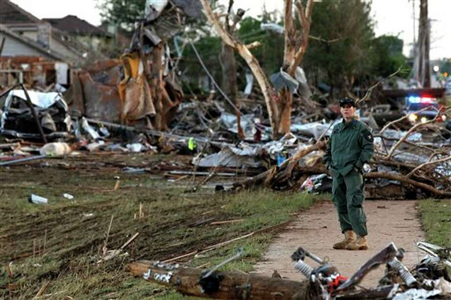 A member of a security team helps guard an area of rubble from a destroyed residential neighborhood, one day after a tornado moved through Moore, Okla., Tuesday, May 21, 2013. The huge tornado roared through the Oklahoma City suburb Monday, flattening entire neighborhoods and destroying an elementary school with a direct blow as children and teachers huddled against the winds. (AP Photo/Brennan Linsley) Photo: Brennan Linsley / AP2013