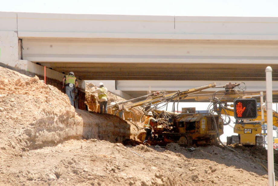 Doug McDonough/Plainview HeraldA crew from Haydon Building Corp. removes dirt from under the north side of the U.S. 70-Interstate 27 overpass to build a turnaround. The Texas Department of Transportation project to convert service roads in the area to one-way began in January and is scheduled to be completed next summer. The overall project is expected to cost at least $17 million.
