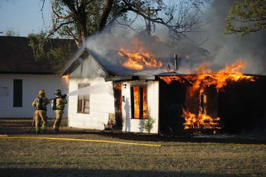 Doug McDonough/Plainview HeraldAn intense blaze discovered about 7:45 p.m. Friday gutted the unoccupied parsonage adjacent to Elim Worship Center, 1310 Galveston. The residence, at 1306 Galveston, appeared to be a total loss while the church suffered some smoke and fire damage after wind-whipped flames ignited eaves in the classroom wing of the structure. According to church members, the parsonage was vacant since Pastor Roger Munoz has his own residence. Utilities to the house were disconnected and outside windows boarded up, they said, because it had been damaged by vandals previously.