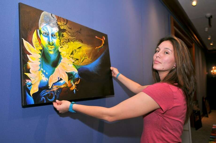 Tatiana González hangs one of her paintings for her senior art show in the Abraham Art Gallery at Wayland. González, an art major from Colombia, will graduate Saturday. Photo: Wayland Baptist University Photo