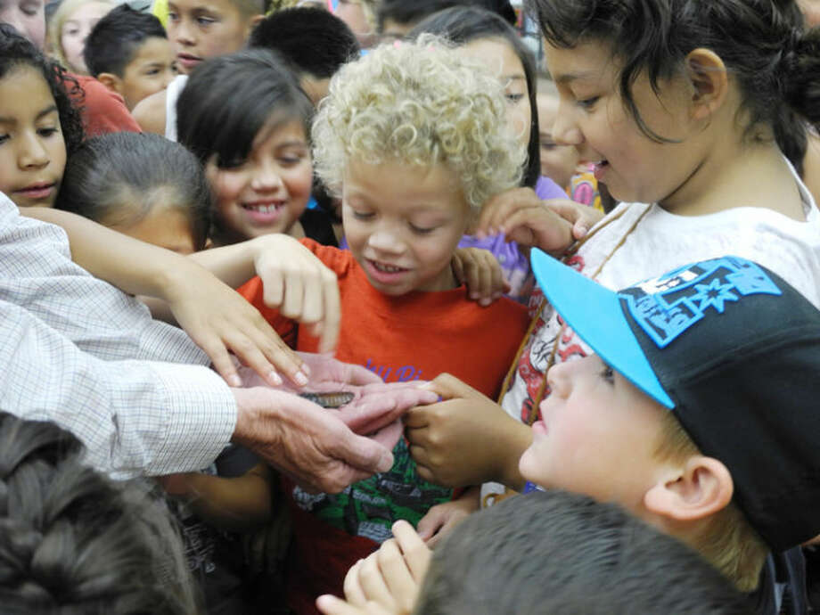 Children gather eagerly for a chance to stroke the hissing roach. Photo: Gail M. Williams | Plainview Herald