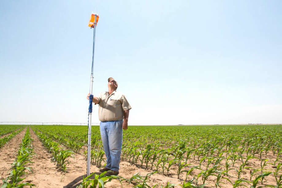 A device that transmits information on soil moisture in a cornfield belonging to David Ford (standing) a farmer near the Texas Panhandle town of Dumas. He is participating in a water-saving demonstration project. Photo: Jerod Foste /Texas Tribune