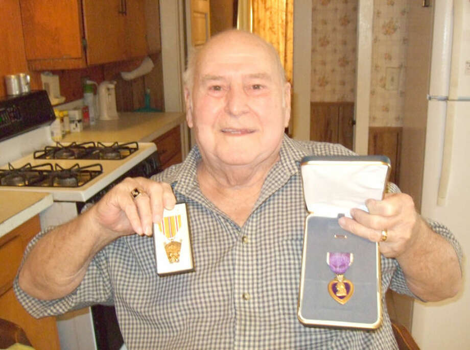 Shanna Iverson/Plainview HeraldWorld War II veteran Calvin White shows his Purple Heart and Asianic-Pacific campaign medals at his Baltimore Street home in Plainview. The 88-year-old was injured in battle by a Kamikaze (Japanese suicide) bomber. When the Navy planned to send him home after the injury, White pleaded to stay and was granted his request before the ship set sail for Japan.