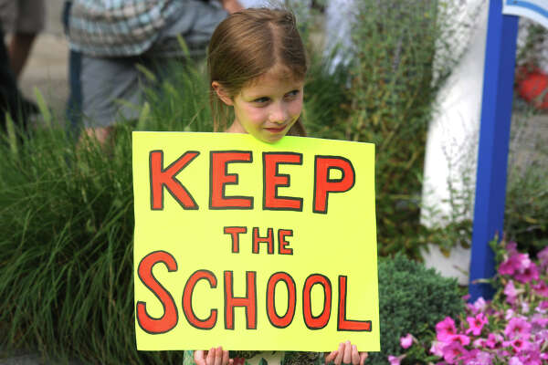 Natasha Schumann, 7, takes part in a protest in Stratford, Conn. July 25, 2016. Most of the group gathered oppose the proposed demolition of Center School to make way for a new parking garage.