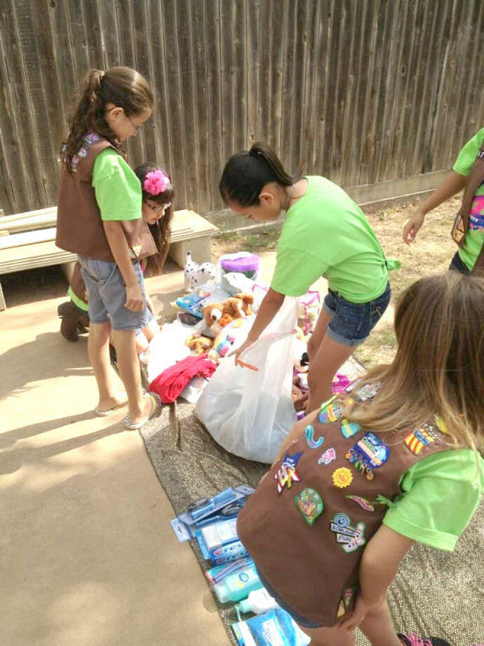 Courtesy PhotoGirl Scouts from Troop 6211 have joined the Moore donation effort by adopting a family in Moore, Okla., which was hit by an F5 tornado in May. The Girl Scouts are shown sorting donations in preparation for sending them to storm victims.