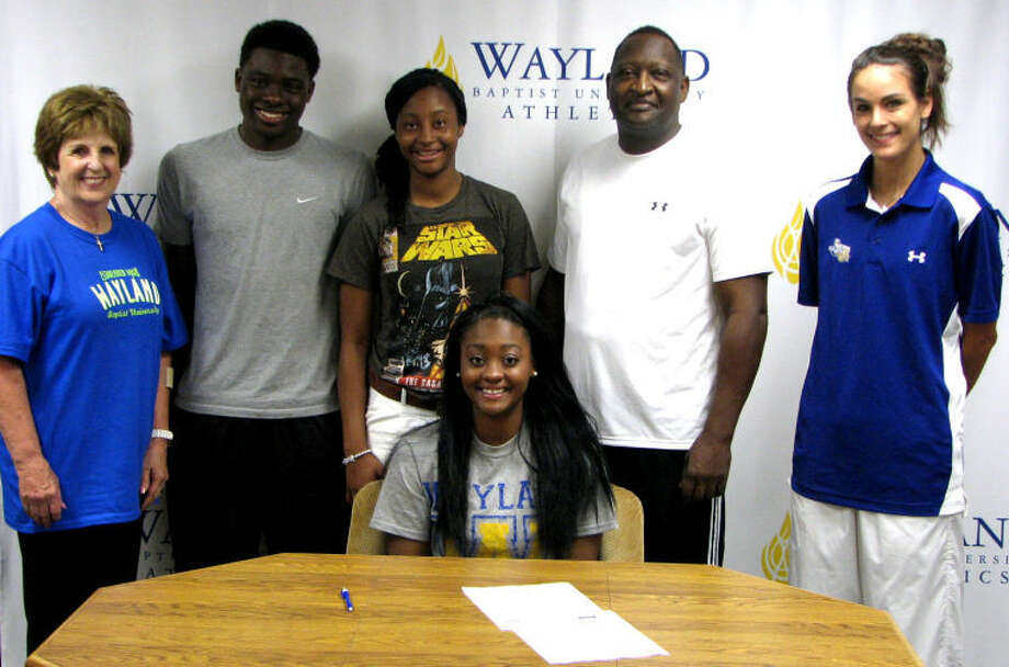 Sydney Hearn signs with the Queens. She is accompanied by head coach Alesha Robertson (right), assistant coach Melynn Hunt (left) and her family. Photo: Wayland Baptist University Photo