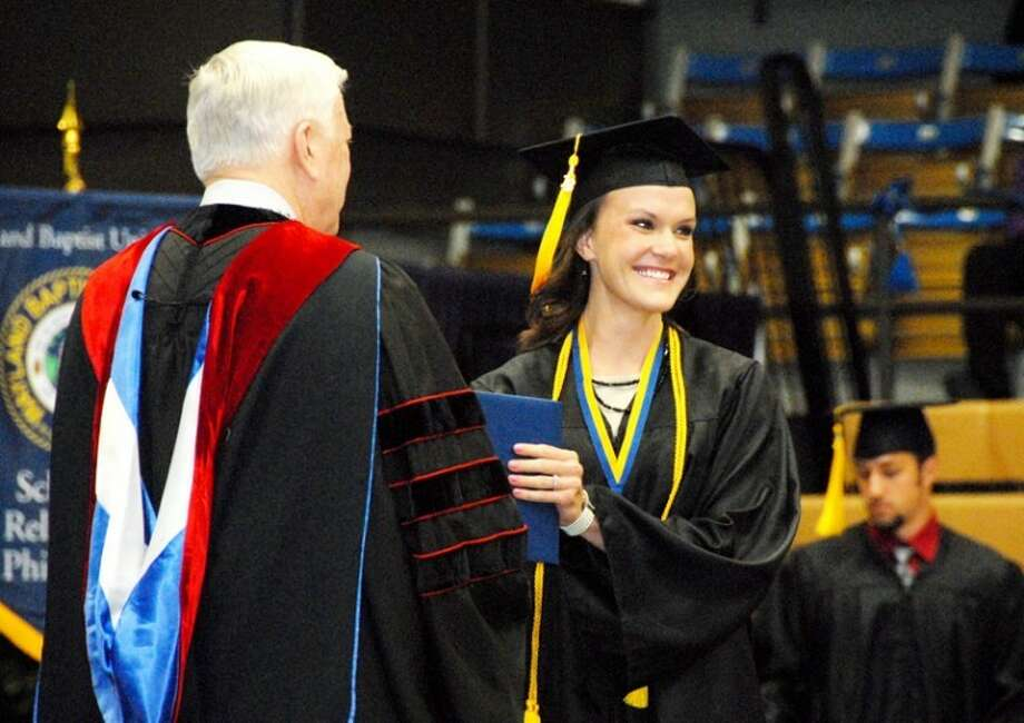 Wayland Baptist University PhotoKimberli Harger of Lubbock is all smiles as she receives her diploma from Wayland President Dr. Paul Armes during Saturday's commencement.
