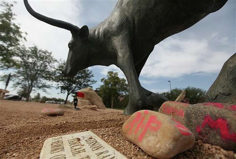 Memorials rest at the feet of a longhorn statue at the National Ranching Heritage Center in Lubbock, Texas, Tuesday, June 25, 2013 where 14-year-old Miguel Martinez died as the result of an accident. Martinez ran into the bull statue while playing hide-and-seek with friends and was impaled on the horn of the statue early Saturday morning, June 22, 2013. (AP Photo/Lubbock Avalanche-Journal,Zach Long) Photo: Zach Long / Lubbock Avalanche-Journal