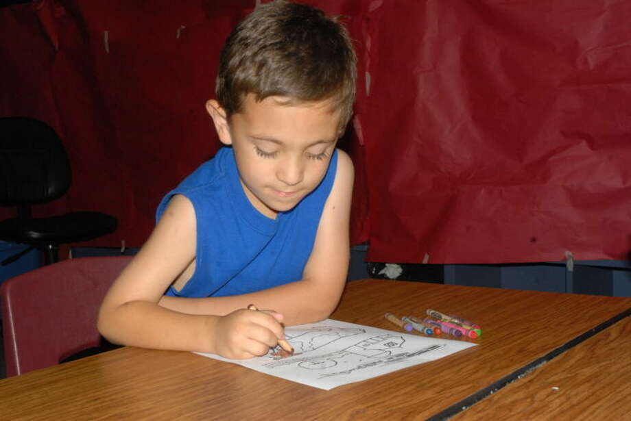 Six-year-old Clayton Juarez watches his lines as he colors his entry in for the Red, White and Moo coloring contest. The winners will be displayed at Saturday's seventh annual Milk Fest, at the Ollie Liner Center. Today, local artists will display their talents up and down Broadway from 5-8 p.m. during the Plainview ArtWalk. Photo: Homer Marquez/Plainview Herald