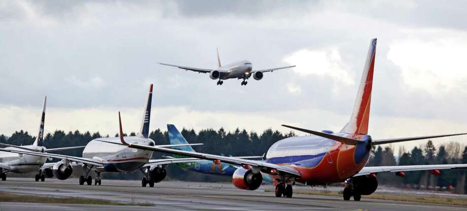 FILE - In this Dec. 16, 2015 file photo, a passenger jet comes in for a landing and in view of a line of planes waiting to takeoff, at Seattle-Tacoma International Airport.  U.S. environmental regulators are moving to limit emissions from aircraft, ruling that jet engine exhaust is endangering human health by warming the planet. The Environmental Protection Agency announced Monday that it will use its authority under the Clean Air Act to regulate aircraft emissions.  (AP Photo/Elaine Thompson) Photo: Elaine Thompson, STF / Copyright 2016 The Associated Press. All rights reserved. This material may not be published, broadcast, rewritten or redistribu
