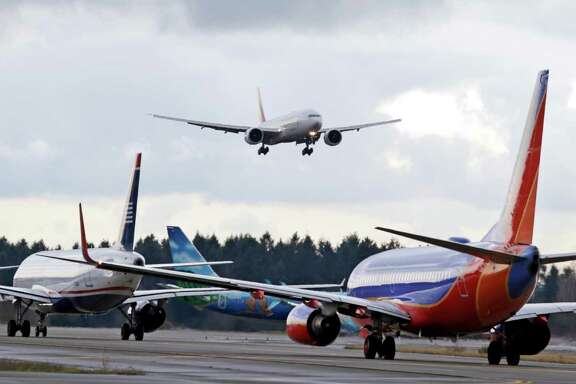 FILE - In this Dec. 16, 2015 file photo, a passenger jet comes in for a landing and in view of a line of planes waiting to takeoff, at Seattle-Tacoma International Airport.  U.S. environmental regulators are moving to limit emissions from aircraft, ruling that jet engine exhaust is endangering human health by warming the planet. The Environmental Protection Agency announced Monday that it will use its authority under the Clean Air Act to regulate aircraft emissions.  (AP Photo/Elaine Thompson)