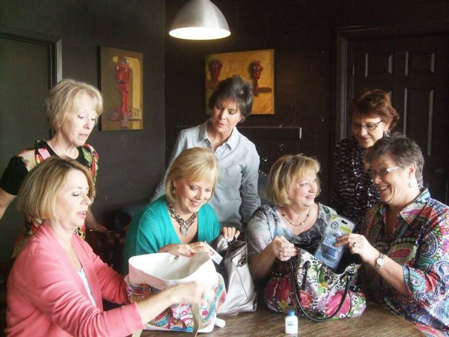 Nicki Bruce Logan/Plainview HeraldPhyllis Wall (standing left), Sally Eaves and Sally Meeks look over the shoulders of Barbara Glodt (left), Jennifer King, Coralyn Dillard and Carol Kaufman as they sort items they will place in purses during their grassroots Help in a Handbag party from 3-4 p.m. Sunday, May 20 at Broadway Brew.