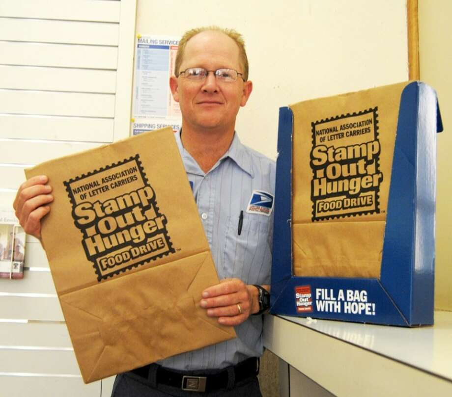 Doug McDonough/Plainview HeraldCity postal carrier Mark Leatherman will join his counterparts nationwide Saturday in collecting food for those in need as part of the 20th annual National Association of Letter Carriers' Stamp Out Hunger food drive. Participating residents should place nonperishable food packaged in non-glass containers next to their mailboxes Saturday morning. Leatherman said they can pick up a sack to use from this display in the post office lobby or put their donations in plastic grocery sacks. Local donations benefit Faith In Sharing House. All donations will be picked up only by letter carriers on their regular rounds.