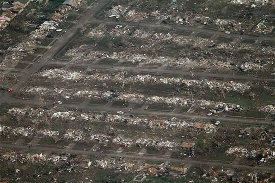 This aerial photo shows the remains of homes hit by a massive tornado in Moore, Okla., Monday May 20, 2013. A tornado roared through the Oklahoma City suburbs Monday, flattening entire neighborhoods, setting buildings on fire and landing a direct blow on an elementary school. (AP Photo/Steve Gooch) Photo: Steve Gooch / AP