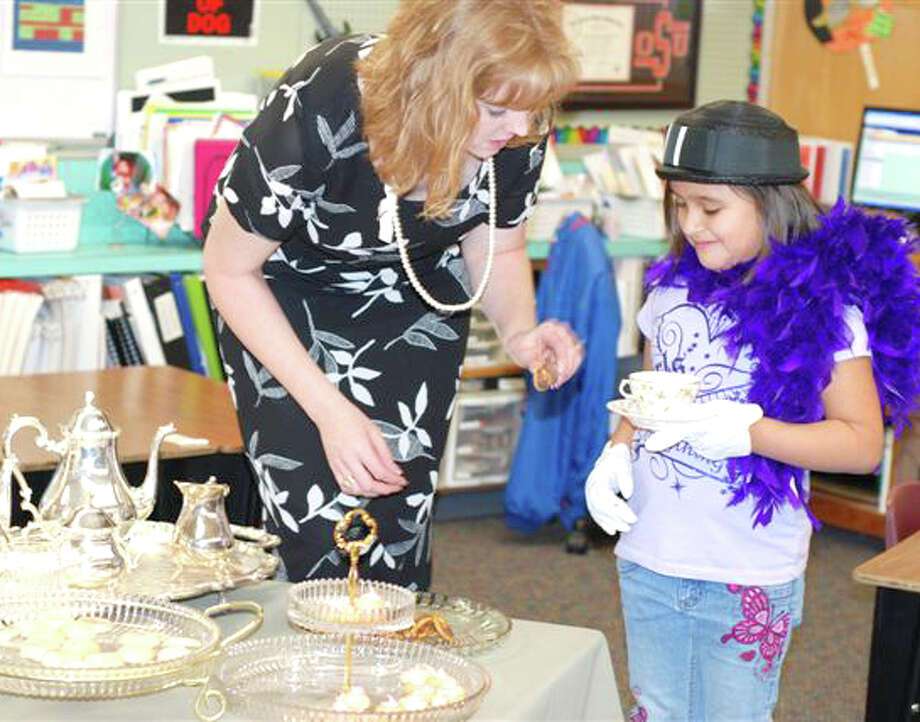 Edgemere first-grade teacher Amber Graves helps student Brandy DeLeon prepare a cup of tea for her mother during the Mother's Day Tea on Thursday.