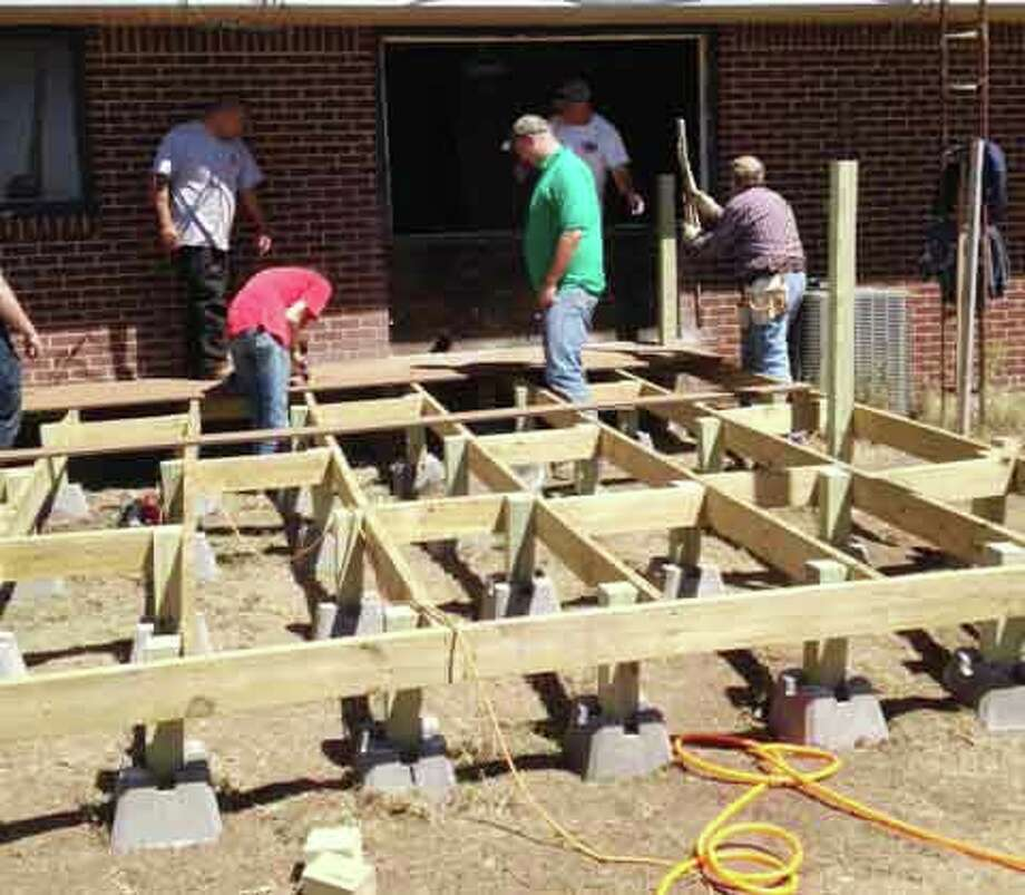 The Men's Ministry of First Baptist Church builds a deck onto Nolan and Janet Bontke's house in order for him to go outside and watch his grandchildren play. Photo: Courtesy Photo