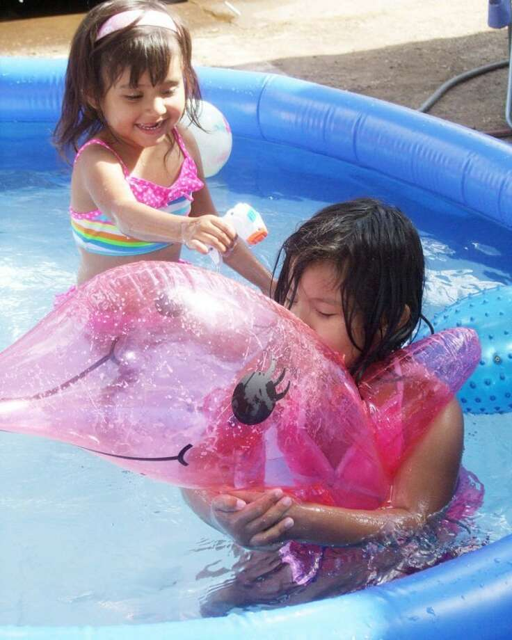 Janessa Torres, 4, sprays water on Maliah Soto, 6, as she rides a pink dolphin around their swimming pool Wednesday afternoon. Janessa and Maliah were enjoying splashing with Sariyah Garcia and Harley Soto, both 4. After three straight days with highs in the 90s, temperatures are expected to soar again starting today. Highs near or above 100 are forecast for at least the next six days, including 107 on Friday. No rain is in the seven-day forecast for our area.