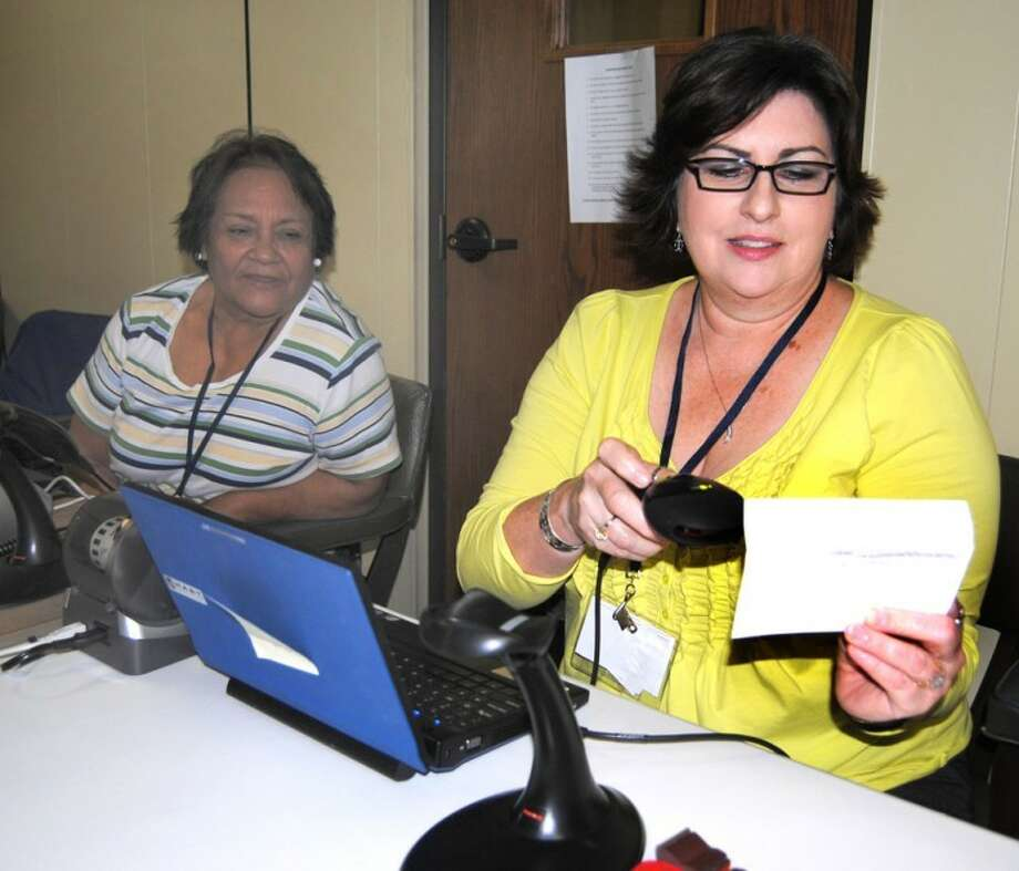 Doug McDonough/Plainview HeraldPoll worker DiAnna Jones uses a scanner attached to a new e-Poll Book computer to read the bar code on a newly-issued voter registration Monday during the first day of early voting for the May 29 primary. Computerized voting rolls have replaced the bulky printed lists that election workers previously had to search to verify a voter's eligibility and mark that they voted. Another election worker, Lupe Castillo, watches the process. Through mid-day Monday, turnout in early voting had been light. Early voting in both the Democratic and Republican primaries continues through May 25 in the basement of the Hale County Courthouse as well as Hale Center City Hall, Abernathy City Hall and Petersburg City Hall. Election day is May 29.