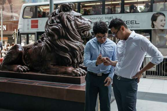 "Office workers play Nintendo's ""Pokémon Go,"" developed by Niantic, on Monday outside the HSBC Holdings headquarters in Hong Kong."