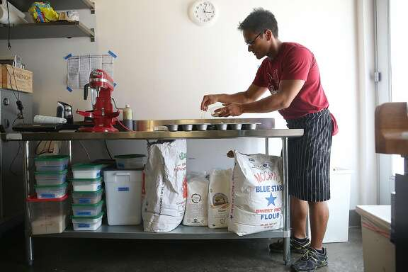 Pastry chef/mochi maker Sam Butarbutar tops Hawaiian Mochi batter with sesame seeds in his kitchen at Catahoula Coffee on Friday, July 22, 2016, in Berkeley, Calif.