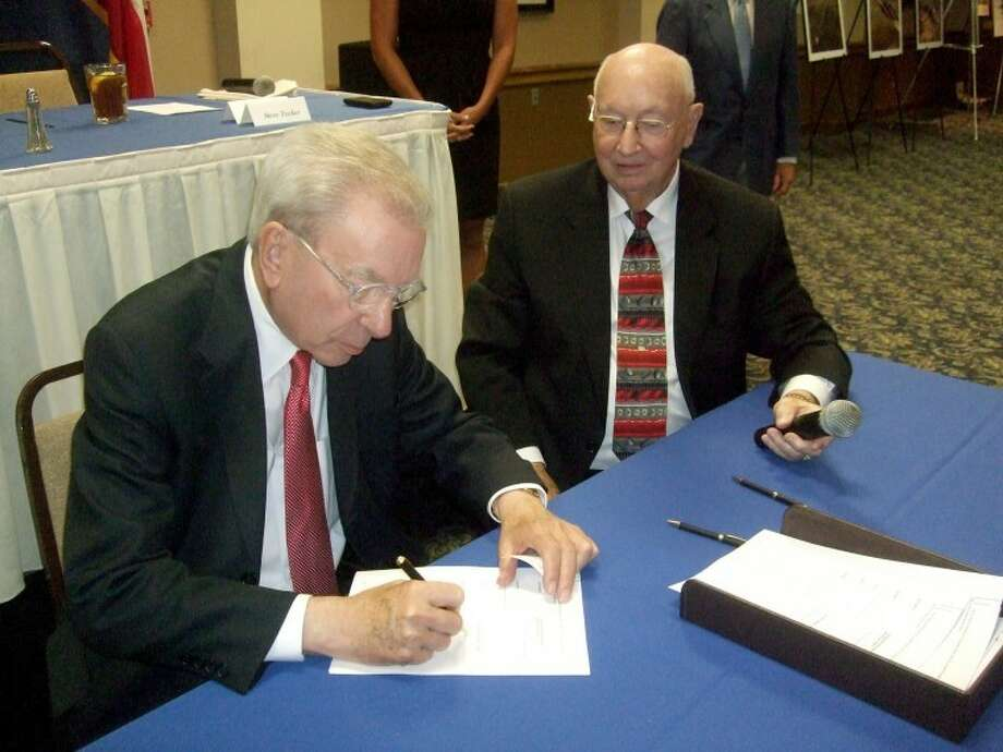 Plainview Mayor John C. Anderson signs the agreement as CRMWA President Norman Wright looks on.