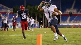Darik Dillard of the Rice Owls scores the game-winning touchdown as Alfred Ansley of the Florida Atlantic Owls looks on during the fourth quarter of the game at FAU Stadium on Oct. 10, 2015 in Boca Raton, Fla.