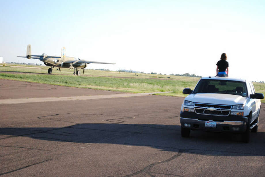 Ryan Crowe/Plainview HeraldMaclane Horan of Plainview looks on as a restored B-25 taxis away after stopping for fuel at Rocket Aviation on its way to California from Florida.