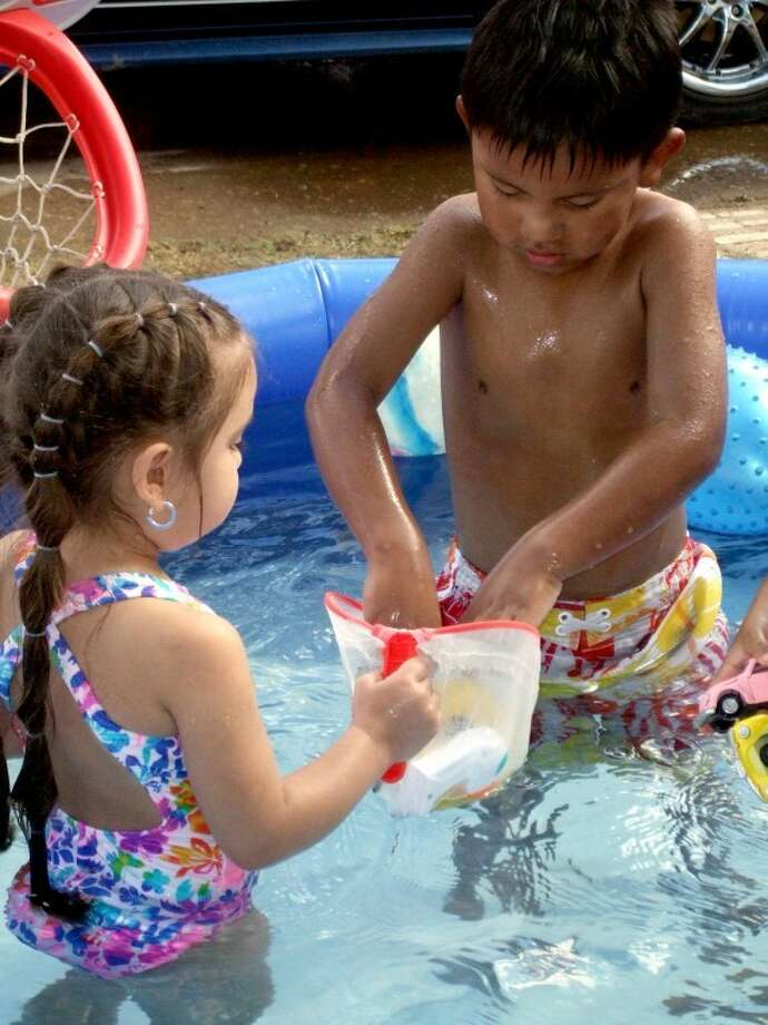 Harley Soto and Sariyah Garcia, both 4, play in a swimming pool to help cool off on a hot afternoon last week.