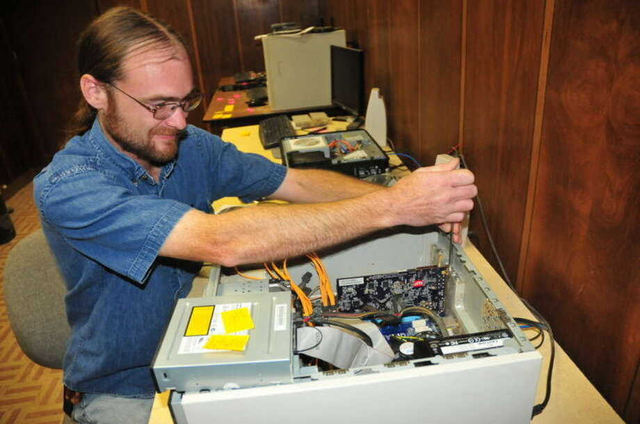 Technician Charles Kissselburg, owner of Kisselburg Computer Repair works on a CPU unit at his shop. Photo: Homer Marquez/Plainview Herald