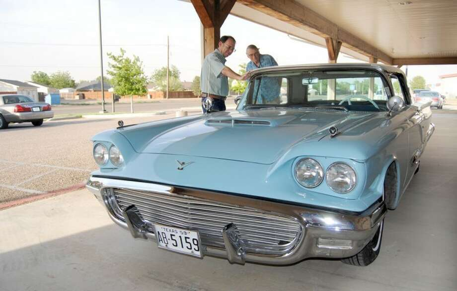 "Blair Willson (left) and John Murcheski inspect S.M. True's 1959 Ford Thunderbird, parked outside Kornerstone Funeral Directors on Friday during family visitation for the nationally-recognized agricultural leader. While on a national farm tour in December 1958, True won the car as a contestant on ""The Price Is Right."" True, 88, died Tuesday in an accident at his farm. Funeral services were Saturday."