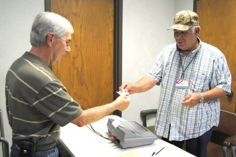 Doug McDonough/Plainview HeraldEarly voter Lee Collum (left) receives a voting machine access code from election worker Stan Foster on Wednesday. Early voting in the May 29 primary ends Friday. As of 3 p.m. Wednesday, 219 mail-in ballots had been received with 556 casting early ballots at the courthouse, 37 at Hale Center City Hall, 45 at Abernathy City Hall and 43 at Petersburg City Hall.