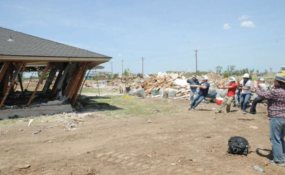 The team from First United Methodist Church pulls on ropes to bring down a house in Moore, Okla. They completed work on one house and demolished another over the course of just three days. Photo: Gail M. Williams | Plainview Herald
