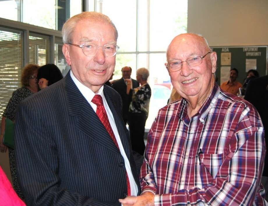 Doug McDonough/Plainview HeraldOutgoing Mayor John C. Anderson (left) shares greetings with Norman Wright during a reception Tuesday at city hall in Anderson's honor. New Mayor Wendell Dunlap recognized both men during the city council meeting for their work in securing water rights in Roberts County for Plainview and other member cities of the Canadian River Municipal Water Authority, for which Wright served as president.