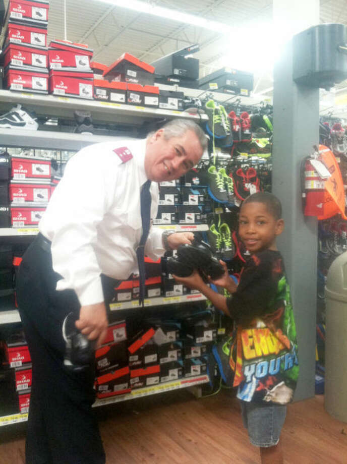 Salvation Army Captain Alfonso Martinez helps upcoming students pick out shoes thanks to the organization's Shoes for Kids program.Courtesy PhotoThe Salvation Army donated 100 pairs of shoes to students during their Shoes for Kids program Monday. Photo: Courtesy Photo