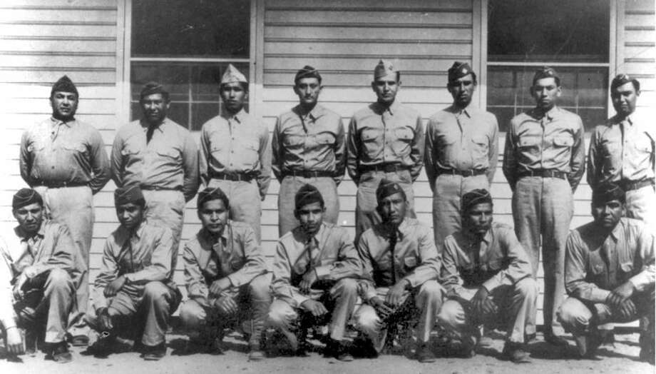 "Photo Courtesy of Barbara & Kenneth Goodin CollectionFort Benning, Ga., 1941: Roderick ""Dick"" Red Elk (front left), Simmons Parker, Larry Saupitty, Melvin Permansu, Willie Yackeschi, Charles Chi-bitty and Willington Mihecoby. Morris Sunrise (back left), Perry Noyebad, Ralph Wahnee, Haddon Codynah, Robert Holder, Albert Nahquaddy, Clifford Ototivo and Forrest Kassanavoid. Not shown are Elgin Red Elk and Anthony Tabbitite."
