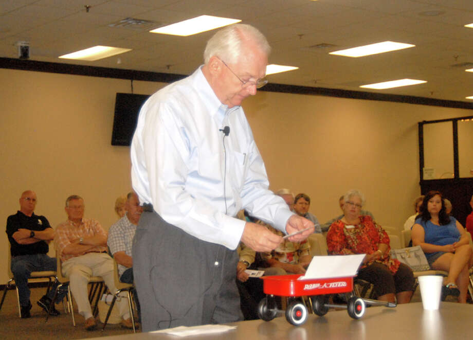 U.S. Rep. Randy Neugebauer reads a question from the audience during Tuesday's local town hall meeting, after first pulling it from his little red wagon. In addition to holding cards with various questions, Neugebauer used the wagon as an illustration for one of his points.