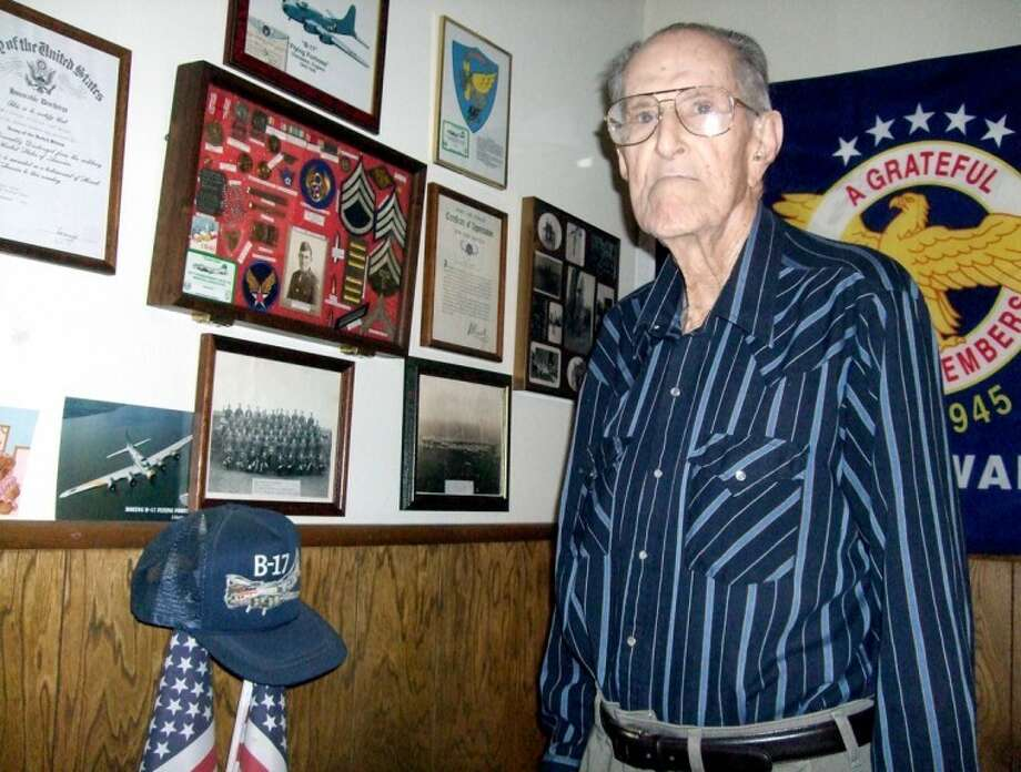 Kevin Lewis/Plainview HeraldSam Thompson looks over his collection of World War II memorabilia in his basement. Thompson was a staff sergeant in the Army Air Force, stationed in England with a bomb group and chemical warfare unit working with B-17s.