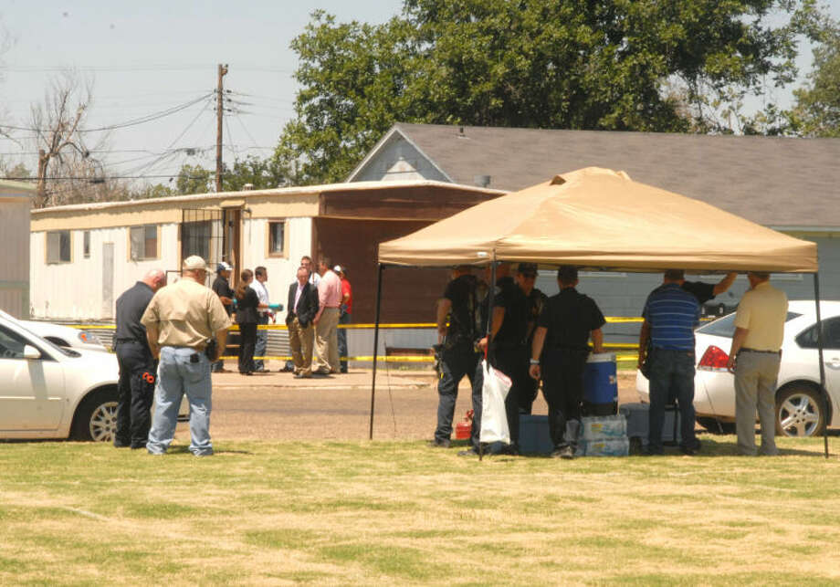 Investigators seek shelter under an open-sided tent while investigating the death of two individuals found in a mobile home Friday across from Plainview High School.