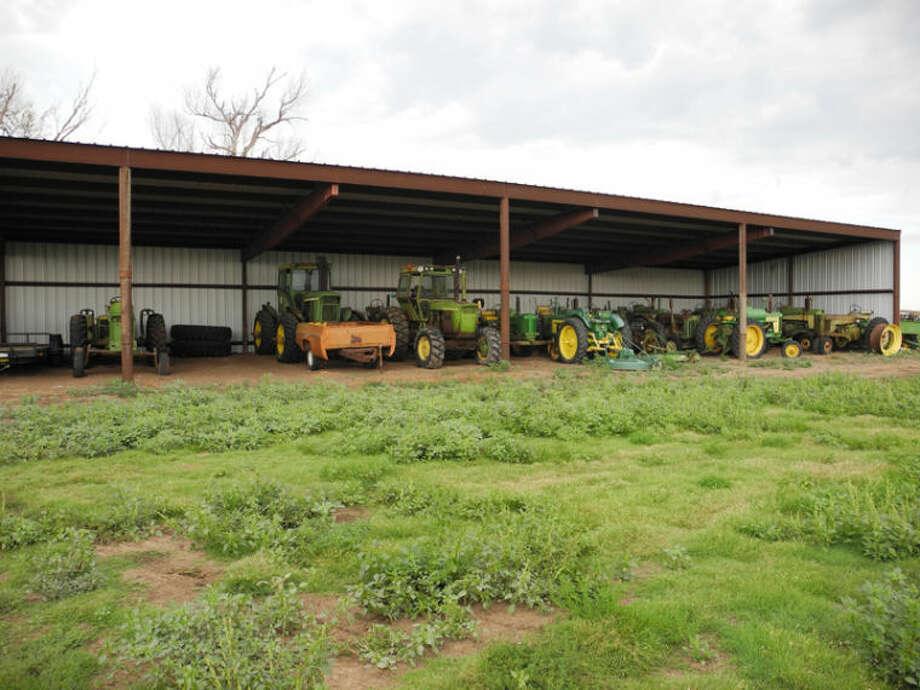 Old John Deere tractors beneath a shelter wait to be restored. Now 38, Kress farmer Cody Gruhlkey has been restoring tractors since he was 19. Photo: Gail M. Williams   Plainview Herald