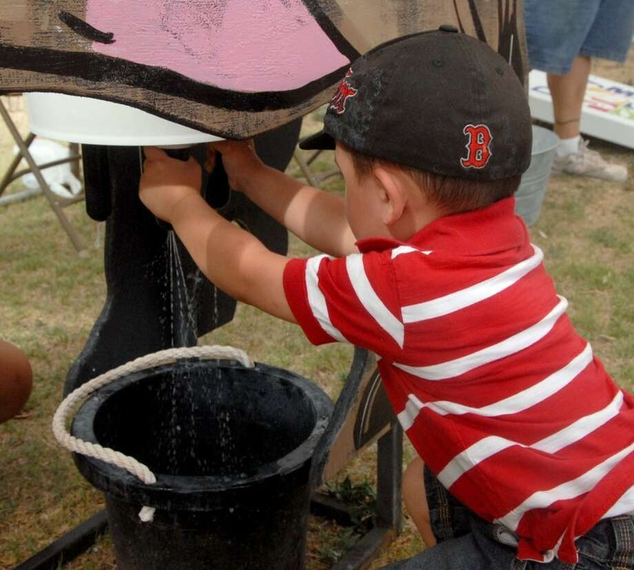 Three-year-old Aiden Suarez learns to milk a cow at this station during the Red, White and Moo Milk Fest at Broadway Park on July 4th. Aiden is the son of Lorraine COntreras.