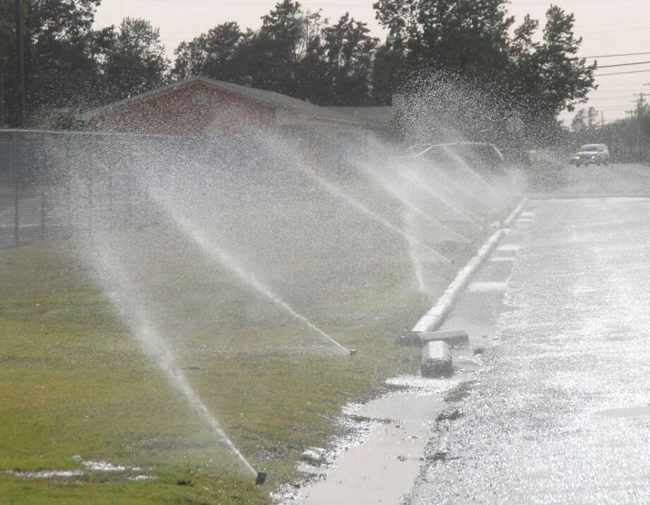 A lot of the water that was intended to fall on the grass actually is being blown onto the street on this windy day a few weeks ago. Local residents and businesses are encouraged to not water their lawns in high-wind situations and to either water early in the morning or later in the evening so high heat won't evaporate the water. Photo: Richard Porter/Plainview Herald