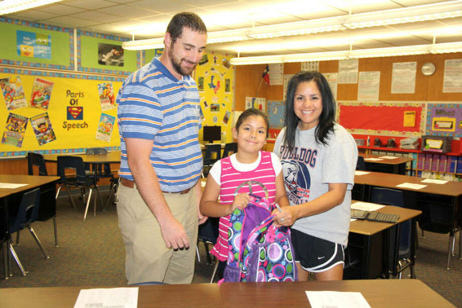 Fourth grade teacher Noah Hall greets new student Demi Vera and her mother Veronica Vera on the first day of school. Hall previously taught at Hillcrest and is new to the Thunderbird staff. At right, pre-kindergarten student Amber Jaquez takes a bite of breakfast pizza on her first morning in school. Amber is a student in Sarah Wallace's class at Thunderbird.Jan Seago/Plainview ISDFifth grade students wait in the Thunderbird cafeteria for the morning bell to ring so they can head to class to begin the first day of school. It is the first time in more than 30 years that fifth grade students have attended school at the elementary campuses. Photo: Jan Seago/Plainview ISD
